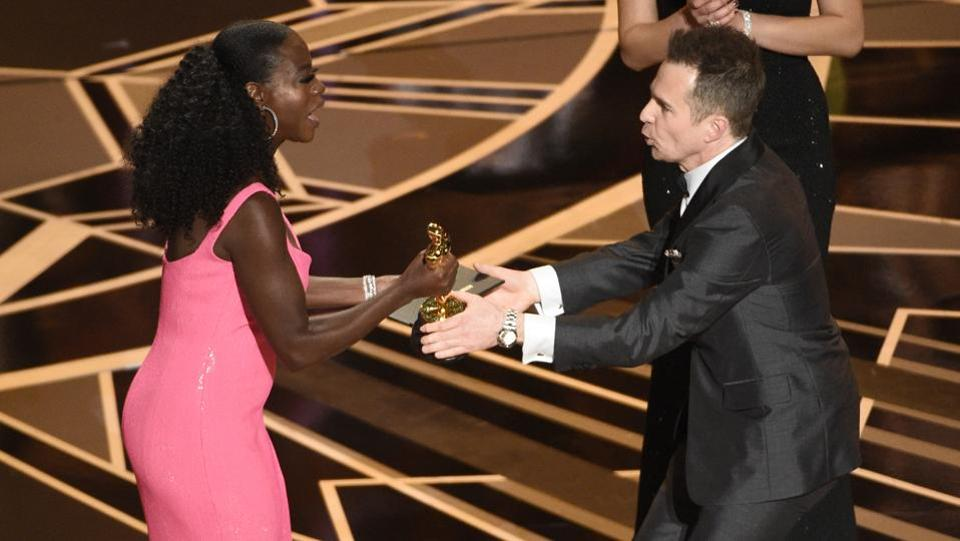 Viola Davis, left, presents Sam Rockwell with the award for best performance by an actor in a supporting role for