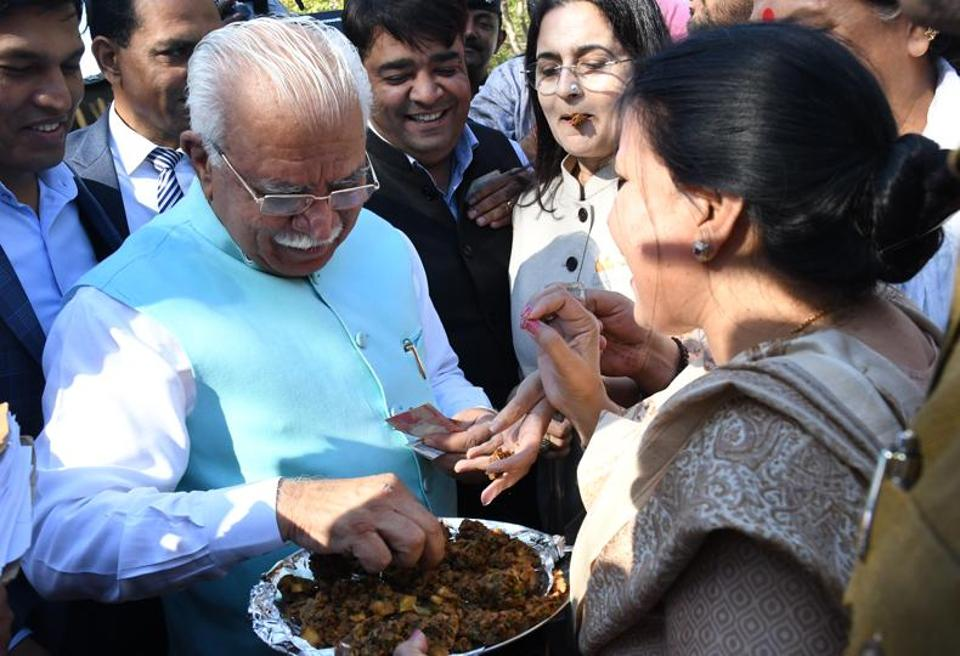 Haryana CM Manohar Lal Khattar  buying 'pakodas' from Congress leaders, who were protesting against Prime Minister Narendra Modi's remarks over job creation, during the budget session at Haryana assembly on Tuesday.