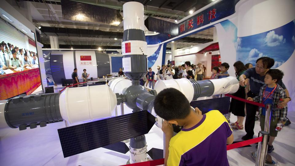 Visitors look at a model of China's Tiangong-1 space station at the China Beijing International High-Tech Expo in Beijing, June 10, 2017.