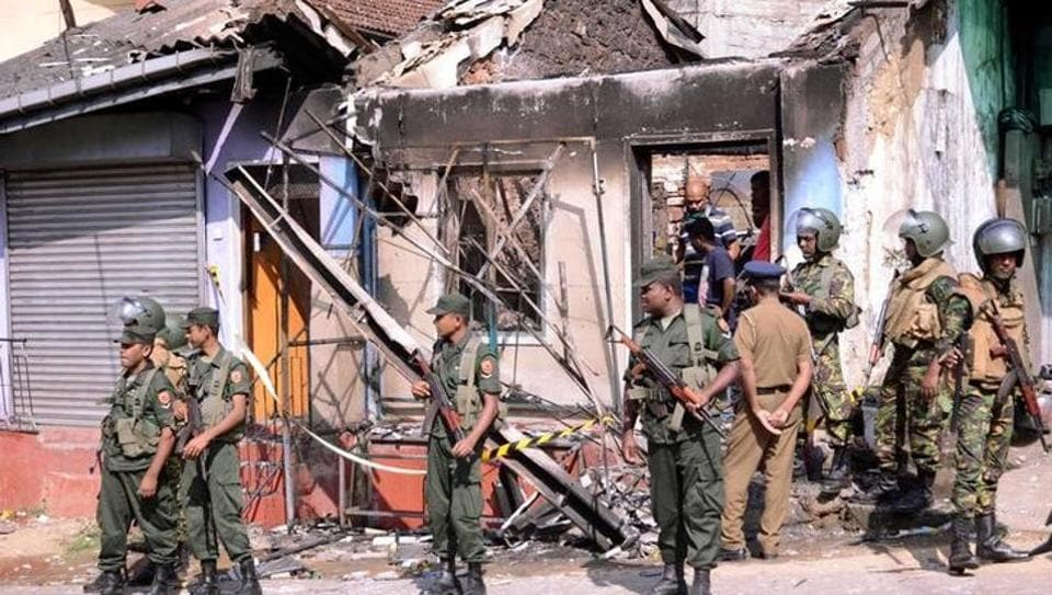 Sri Lanka's Special Task Force stand guard near a burnt house after a clash between two communities in Digana, central district of Kandy, on Tuesday.