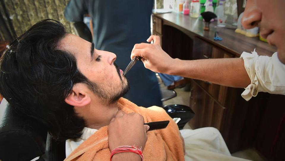 A Pakistani hairdresser styles the beard of a customer at a hair salon in Peshawar on March 6, 2018. Hairdressers in Pakistan's conservative northwest have announced a ban in their shops on 'fashionable' beards, saying trendy facial hair violates Islamic law.