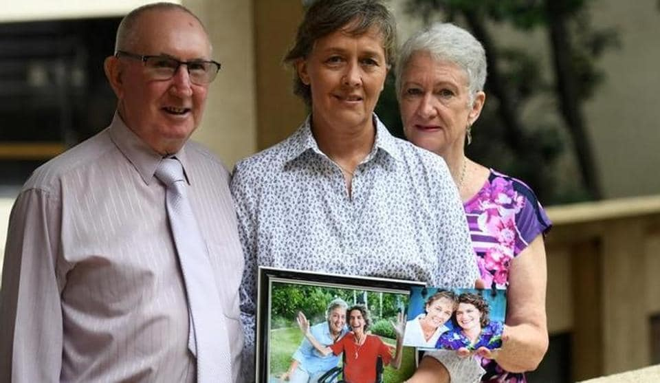 Jill Kindt holds a photo of her with her late wife Jo Grant, joined by Jo's mother Sandra Kelly and her husband Paul at Parliament House in Brisbane on Wednesday.