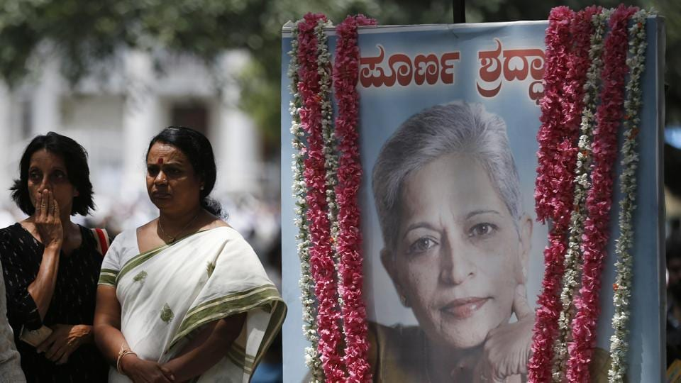 Mourners stand next to a portrait of Gauri Lankesh during the public viewing of her body in Bengaluru.