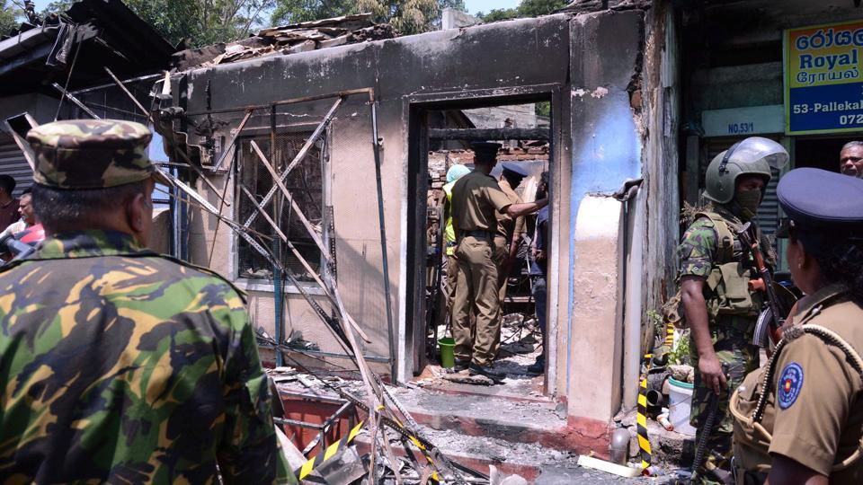 Sri Lanka's Special Task Force and Police officers stand guard near a burnt house after a clash between two communities in Digana, central district of Kandy, Sri Lanka March 6, 2018.