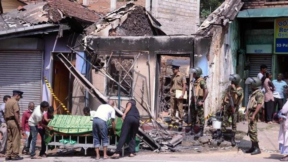 Sri Lanka's Special Task Force and police officers stand guard near a burnt house after a clash between two communities in Digana, central district of Kandy, on Tuesday.