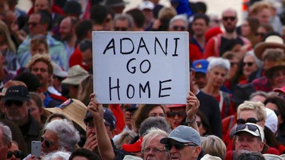 A protester holds a sign as he participates in a national Day of Action against Adani's planned coal mine project in north-east Australia, at Sydney's Bondi Beach in Australia.