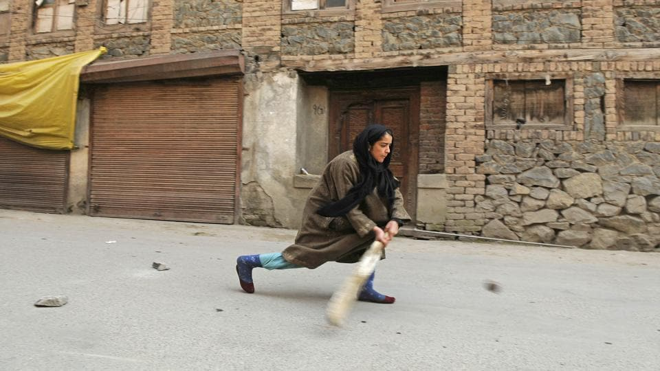A Kashmiri girl plays cricket on a street during restriction in downtown area of Srinagar. Authorities on Wednesday imposed restrictions in parts of Srinagar and Shopian district to maintain law and order in view of a strike and a protest march called by separatists against shifting of Kashmiri prisoners out of the Valley and killings in a firing incident on Sunday. (Waseem Andrabi  / HT Photo)