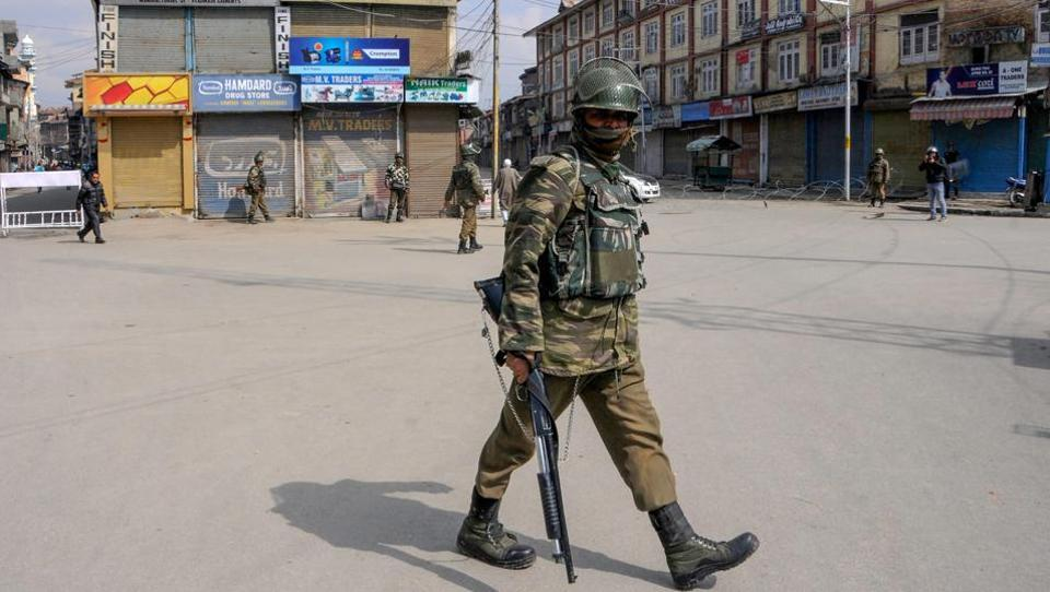 Security personnel guard a street during curfew-like restrictions imposed by the authorities to maintain law and order on Monday.