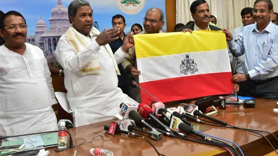 "The Siddaramaiah-led Karnataka government unveiled a state flag on Thursday.The flag design will now be sent to the Central Government for approval, following which it will be announced as the state flag. The unveiled flag consists of three colors- red, white and yellow and has state emblem ""Ganda Bherunda"", a two-headed mythical bird in the middle. (ANI)"