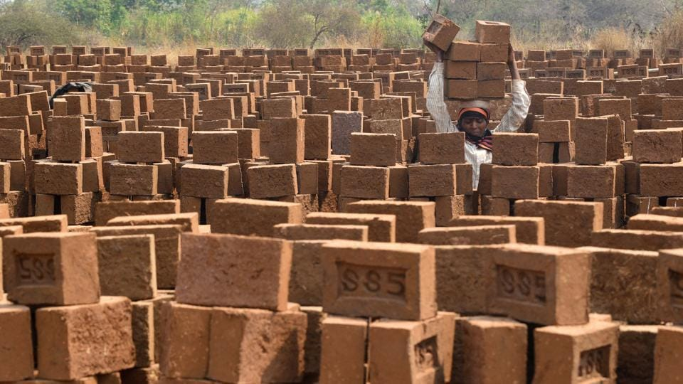 A woman working in a brick kiln located near Pirangut in Pune. Women along with their husbands toil at the unit from 3 am to 6 pm, and eagerly wait for a one-hour break they get for lunch at noon. They migrate from other places to labour at the unit from October to June, as the kiln is shut during the monsoon. When these workers are not working in kilns, they are often working in agricultural fields at their native places. (Pratham Gokhale/HT Photo)
