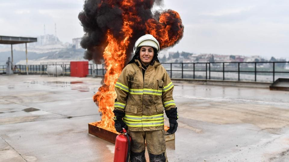 "A female firefighter Devrim Ozdemir poses for  photographs during a training session in Izmir. ""In the beginning, my family told me: 'Stop, you won't succeed, this is a job for men',"" said Ozdemir, who did not heed the advice. In 2008, she became one of the first women to put on a firefighter's uniform in Turkey. (Bulent Kilic / AFP)"