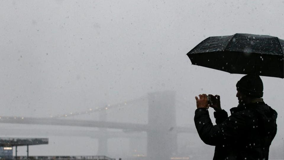 A man photographs the Brooklyn Bridge during a winter nor'easter storm in New York City on March 7, 2018.
