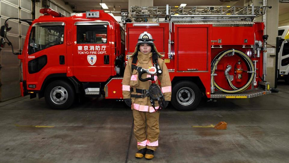Ran Namise, 24, a firefighter belonging to the command squad, poses for photographs  in front of a fire engine at Kojimachi Fire Station in Tokyo. (Kazuhiro Nogi / AFP)