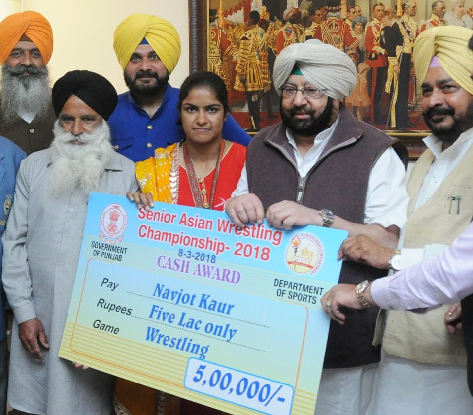 Punjab CM Captain Amarinder Singh presenting a Rs 5 lakh cheque to Navjot Kaur in Chandigarh on Thursday.