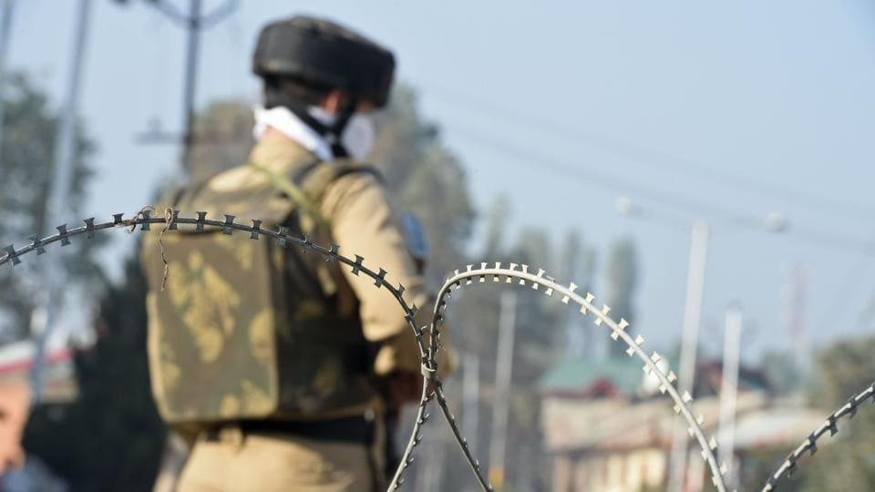 Policeman stands guard near the site of gunfight between suspected militants and government forces in Srinagar.