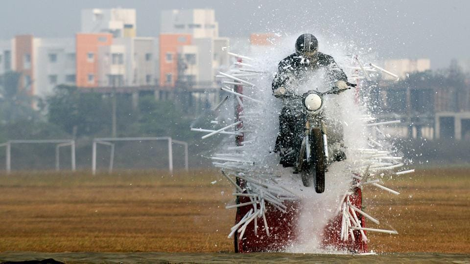 An Indian army member of the 'Tornadoes' motorcycle team rides through tube lights during a combined display at an officer training academy in Chennai on March 9, 2018. (Arun Sankar / AFP)