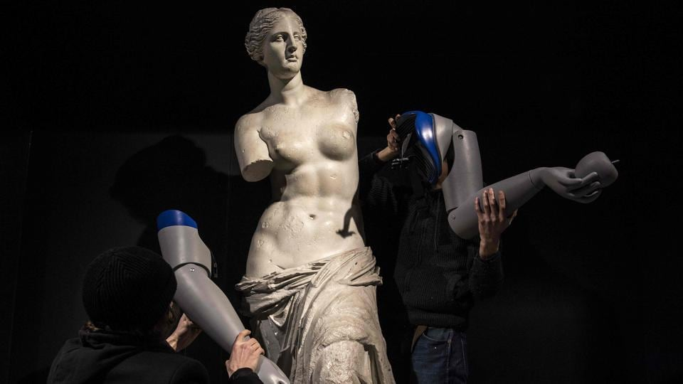 Men dismantle the symbolicly attached prosthetic arms from a replica of the Venus de Milo during an action led by Handicap International to raise awareness on amputees worldwide in need of a prosthesis, at the Louvre-Rivoli metro station in Paris. (Christophe Archambault / AFP)