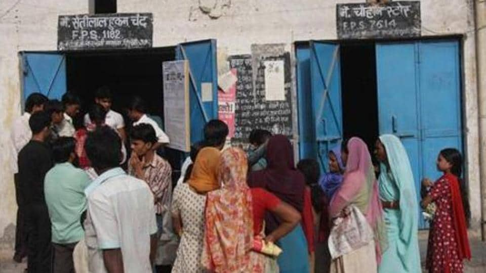 People queue outside a ration shop in Bawana.
