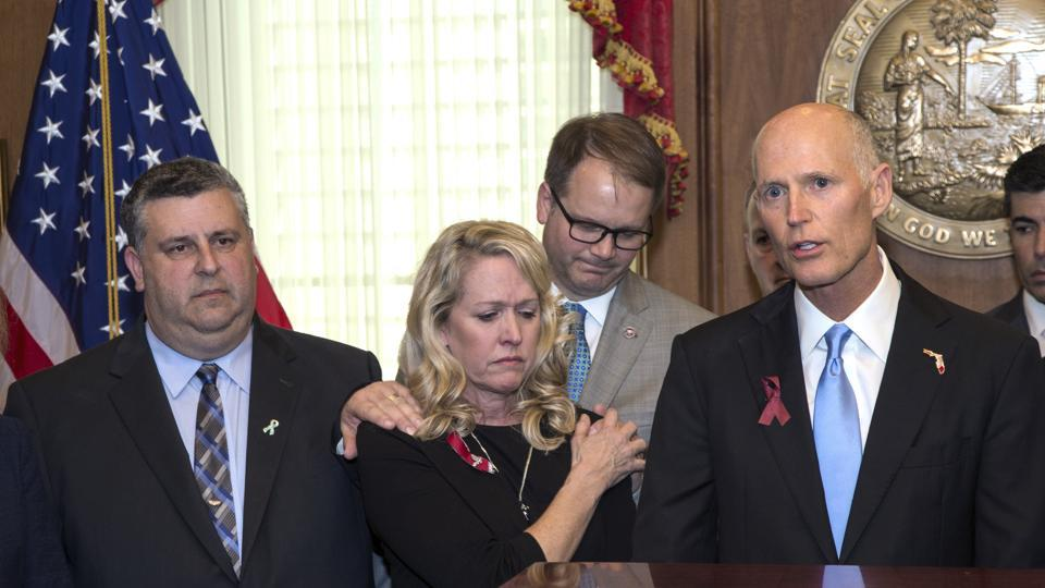 Parents of Florida shooting victim comfort each other as they stand next to Florida governor Rick Scott before he signs the Marjory Stoneman Douglas Public Safety Act in the Governor's office at the Florida Capital in Tallahassee.