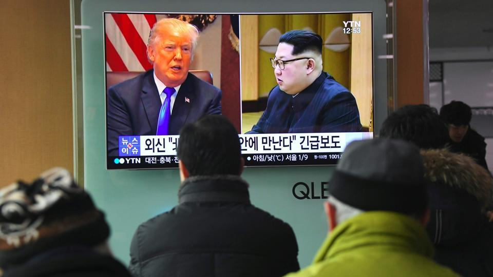 People watch a television news report showing pictures of US President Donald Trump (left) and North Korean leader Kim Jong Un at a railway station in Seoul on March 9, 2018. Trump agreed on March 8 to a historic first meeting with Kim Jong Un in a stunning development in America's high-stakes nuclear standoff with North Korea.