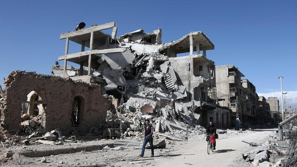Syrians walk past destroyed buildings in the rebel-held town of Hamouria, in the besieged Eastern Ghouta region on the outskirts of the capital Damascus.