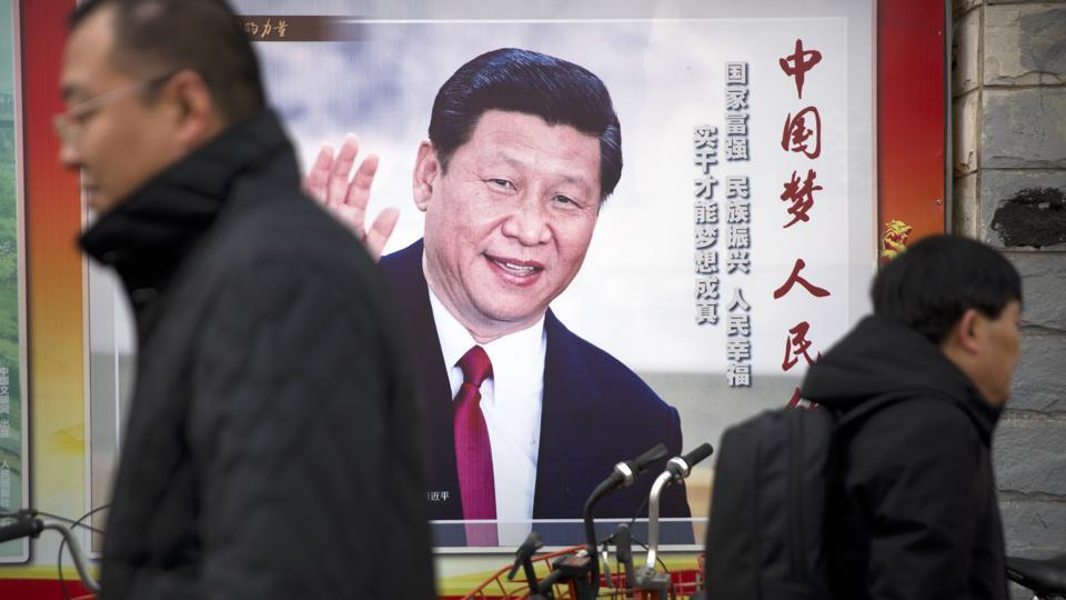Residents walk past a poster showing Chinese President Xi Jinping in Beijing.