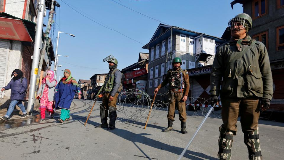 Policemen stand guard on a road after in Srinagar.