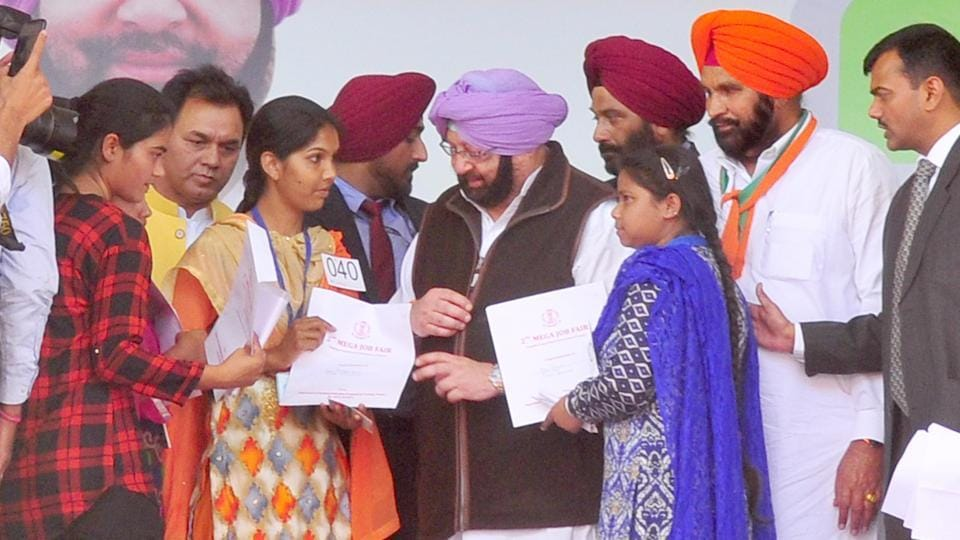 Punjab chief minister Captain Amarinder Singh handing over appointment letters to candidates during a job fair at PAU in Ludhiana on Sunday.