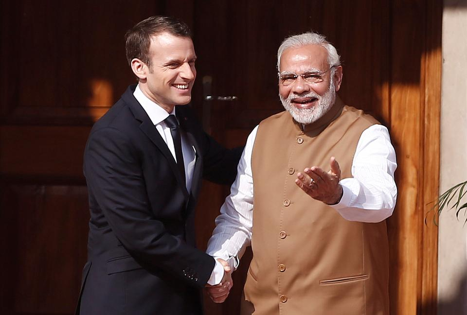 Prime Minister Narendra Modi (R) shakes hands with French President Emmanuel Macron in New Delhi, March 11, 2018.  The visit of the President of France, Emmanuel Macron, saw a Joint Strategic Vision of India-France Cooperation in the Indian Ocean Region, and this document refers to India's central position in the 'Indo-Pacific',