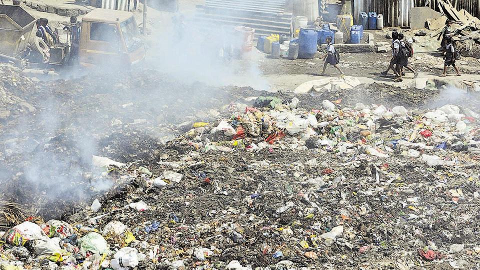 School children walk past an illegal garbage dump yard at Wagholi.