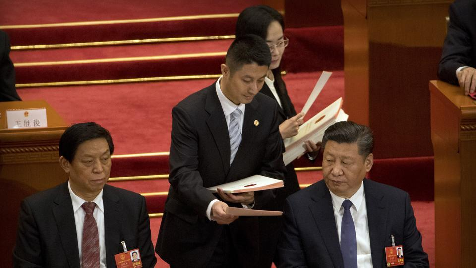 An official hands a ballot to Chinese President Xi Jinping, right, during a plenary session of China's National People's Congress (NPC) at the Great Hall of the People in Beijing, March 11, 2018. China's parliament passed a historic constitutional amendment abolishing presidential term limits that will enable Xi to rule indefinitely. At left is Politburo Standing Committee member Li Zhanshu.