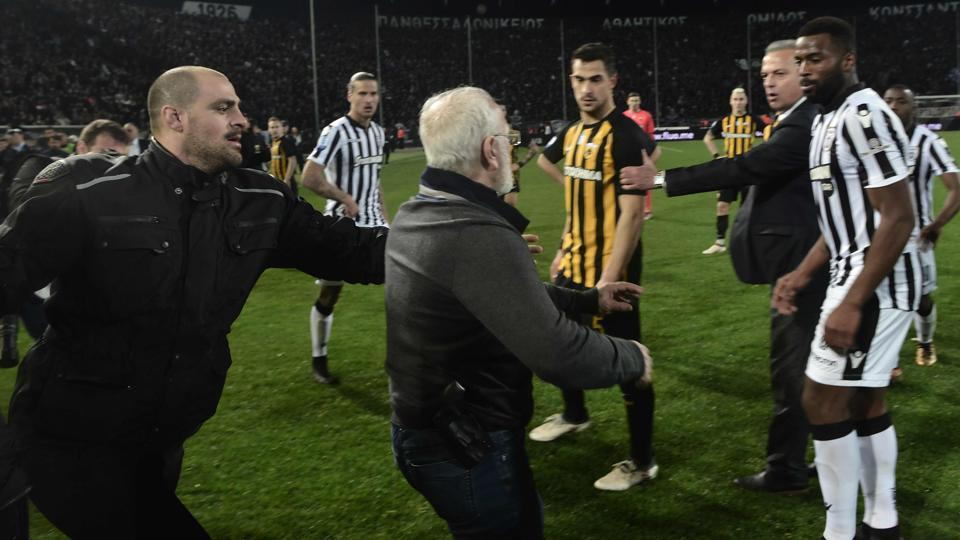 PAOK Thessaloniki owner Ivan Savvidis takes to the pitch carrying a handgun in his waistband during a Greek Super League football match.