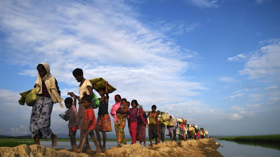 (FILES) In this file photo taken on November 2, 2017, Rohingya Muslim refugees who were stranded after leaving Myanmar walk towards the Balukhali refugee camp after crossing the border in Bangladesh's Ukhia district.