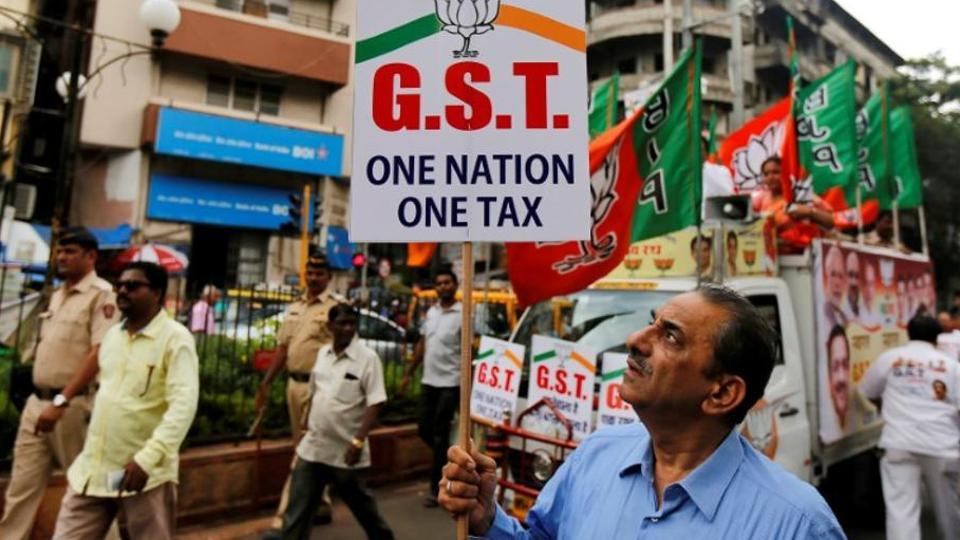 A supporter of the Bharatiya Janata Party holds a placard during a rally to support implementation of the Goods and Services Tax (GST) in Mumbai on June 30, 2017.