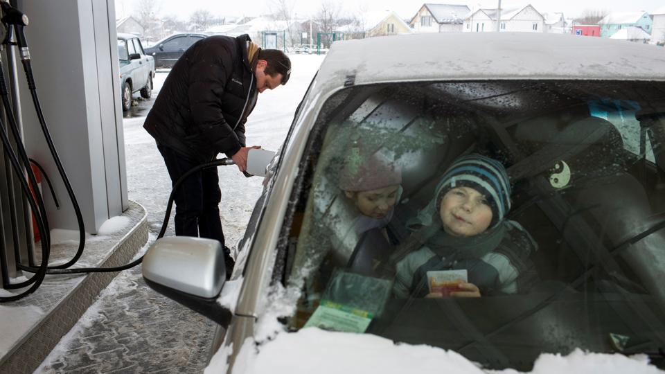 Dmitriy Rozumiy fills his car with gas while his children wait inside the car. Last October, parliament approved a long-delayed overhaul of the health system following international pressure. But times remain tough, forcing Rozumiy to consider halting some home visits as he cannot afford the petrol for his car on a salary of around 6000 hryvnias ($230) per month. (Gleb Garanich / REUTERS)