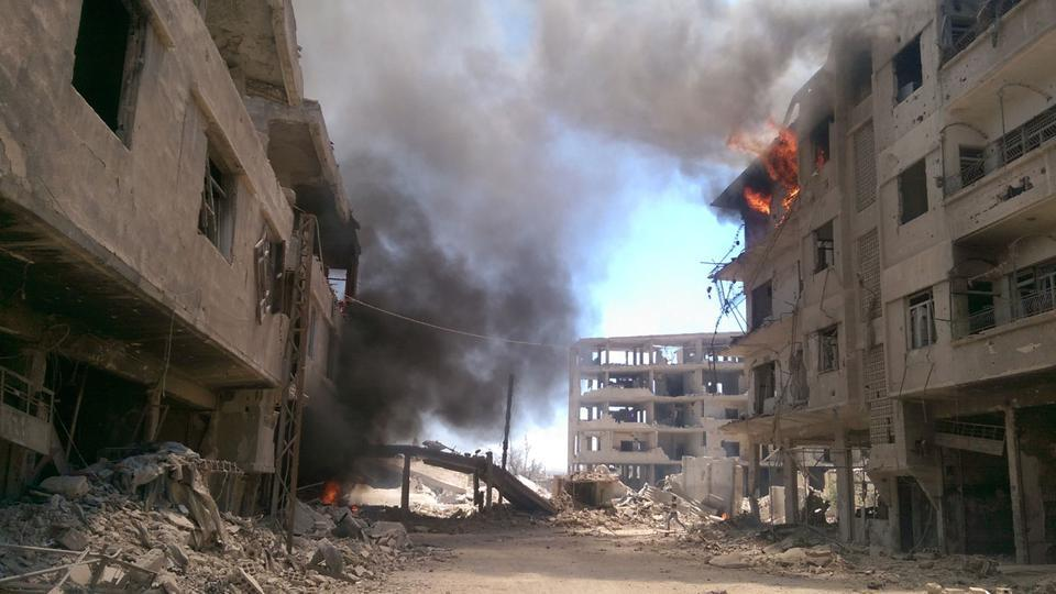 Fire and smoke gush out of buildings following reported air strikes on the Syrian besieged rebel-held town of Daraya near the capital Damascus on August 16, 2016.