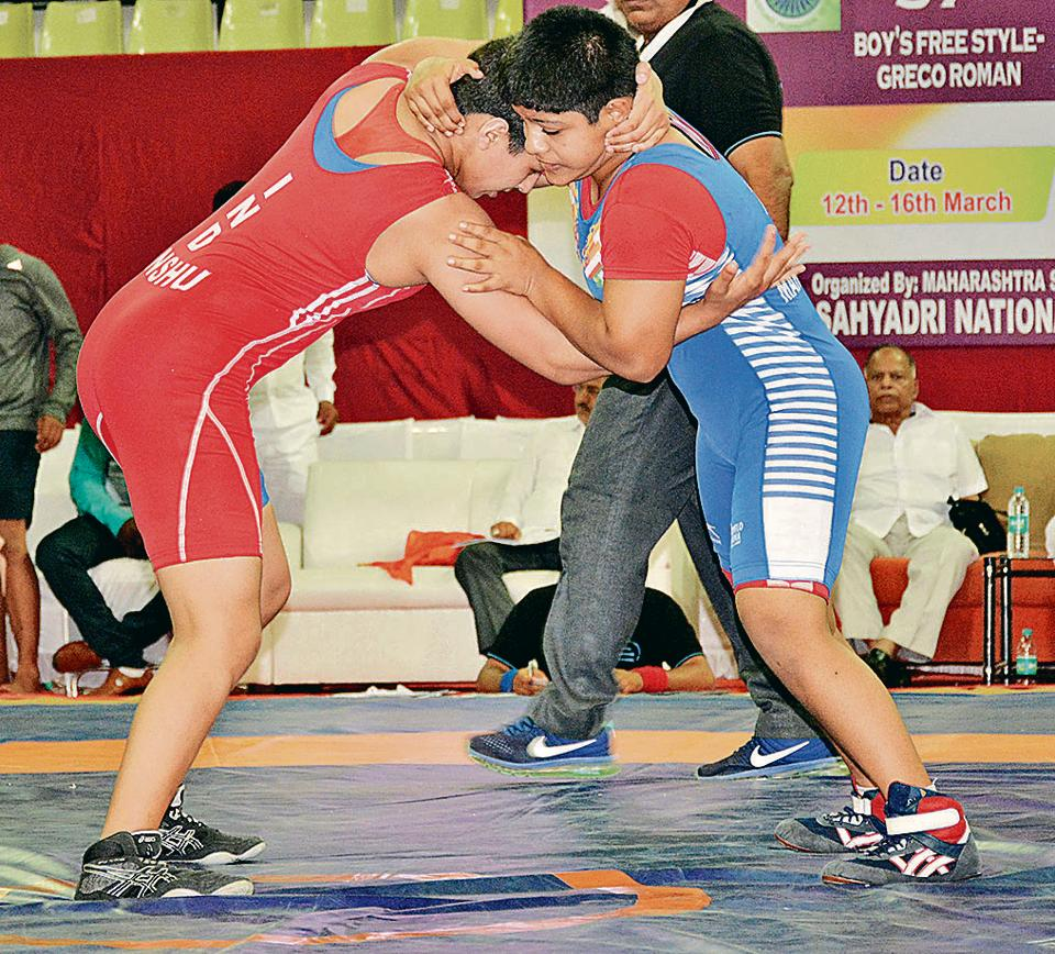 Maharashtra's Srushti Bhosale (61kg) in action against Haryana's Anshu (red) on day one of the 37th sub-junior national wrestling tourney in Balewadi.