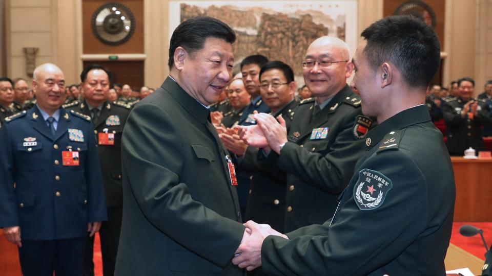 In this photo released by Xinhua News Agency, Chinese President Xi Jinping (centre) shakes hands with delegation of People's Liberation Army and armed police during a meeting in Beijing, Monday.
