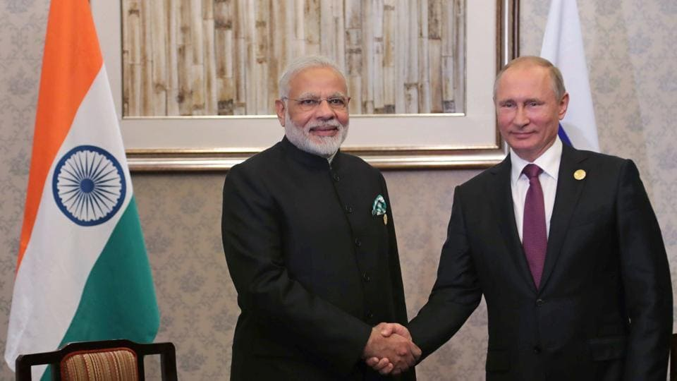 Russian President Vladimir Putin (R) shakes hands with Prime Minister Narendra Modi during their meeting at the BRICS Summit in Xiamen on September 4, 2017.