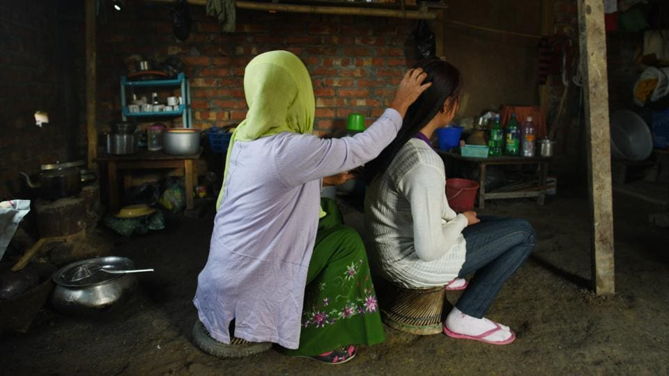 A Manipuri girl who was rescued from Yangon in 2017 at home with her mother. A promise of employment --as a housemaid or babysitter, with food and accommodation, in Singapore, Thailand or China while earning 500 Singapore dollars a month-- is irresistible for both the parents and girls. The network usually involves three sets of agents – one in India, the other in Myanmar and the last in the destination country. (Vipin Kumar / HT Photo)