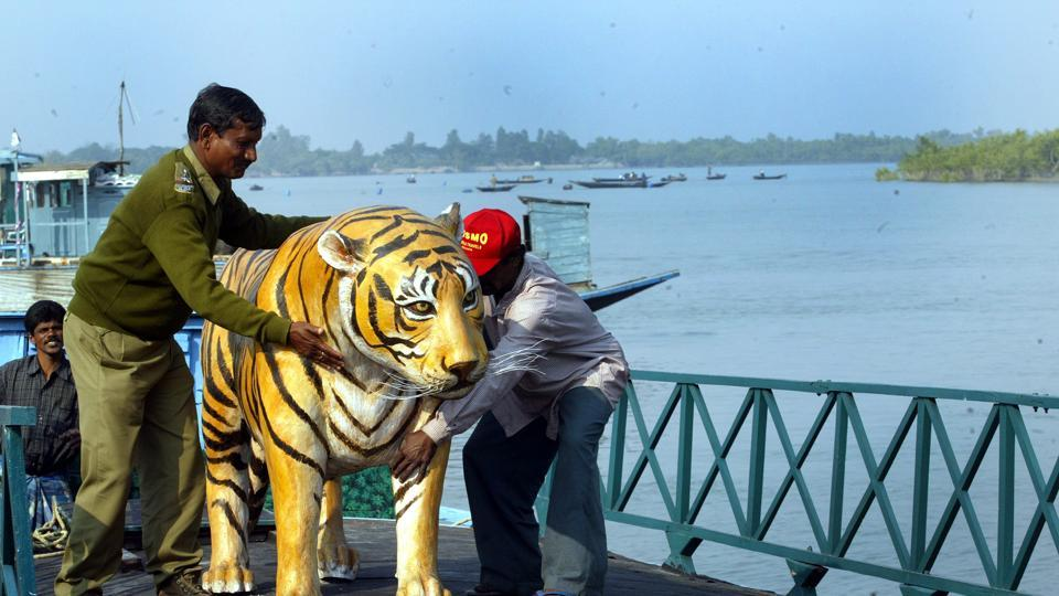 Forest guards hold a model of a tiger at the Sanzekhali Tiger Reserve in the Sunderbans magrove forest delta, January 12, 2004.