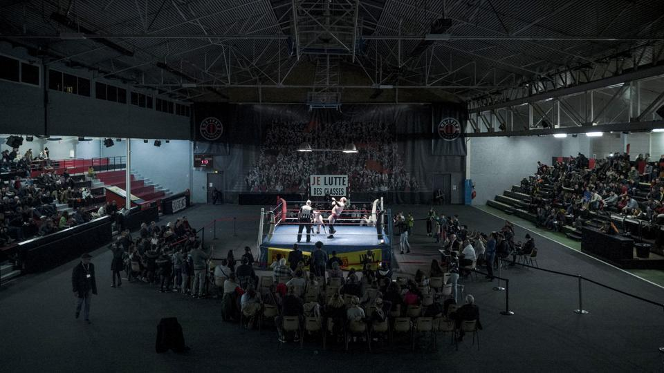 A crowd watches Darkmundo and Alex Legrand fighting during a one-on-one match. Muscles bulging, hair flying, the wrestlers put on quite a show — with losers tossed out of the ring in the grand finale. But the aim of the catch wrestling gala in the communist-run Parisian suburb wasn't to make a profit or showcase celebrities. (Kamil Zihnioglu / AP)