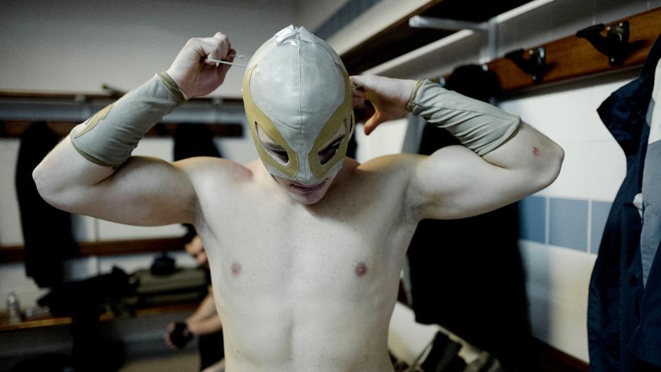 Wrestler Ace Angel ties his mask before heading out. The event was celebrating the anniversary of a charity group called the Association for Employment, Information and Solidarity with the Unemployed and At-Risk Workers. (Kamil Zihnioglu / AP)