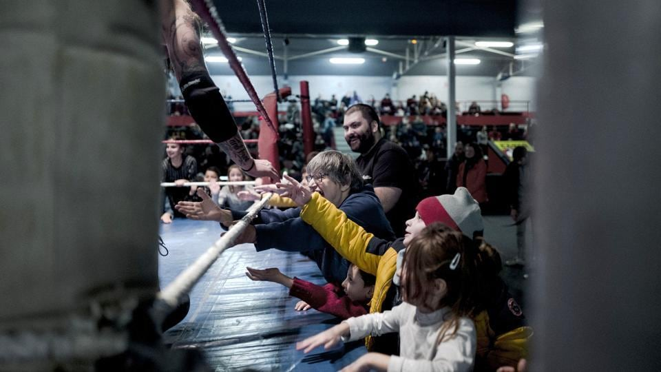 Wrestler Zack claps hands with children during a wrestling match. Entry was free for kids and just 8 euros ($10) for the rest, and the 1,200-capacity hall was full. Funds went to the non-profit association. (Kamil Zihnioglu / AP)