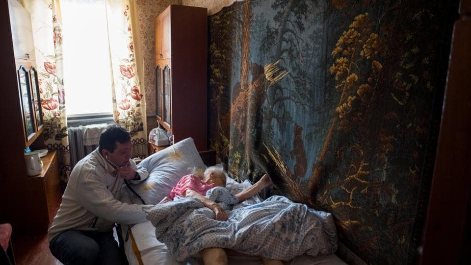 Rozumiy examines an elderly patient at her home in the village of Ivankovichy. He said recent positive changes include the launch of programmes to improve treatment for veterans and help pensioners gain access to certain medicines. (Gleb Garanich / REUTERS)