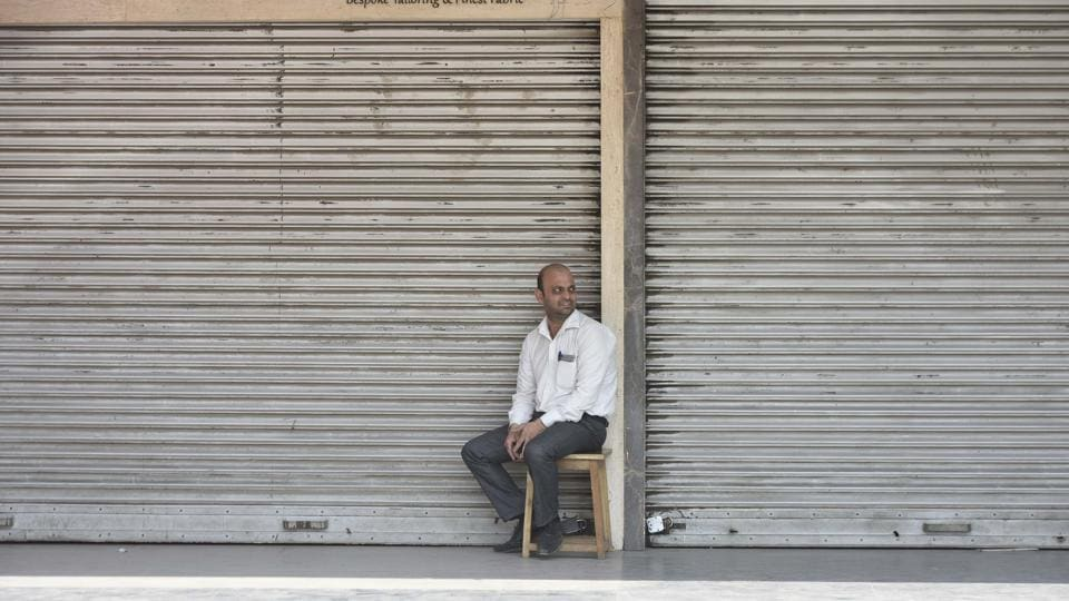A shopkeeper sits in front of a shop at South Extension Part I as traders on Tuesday decided to observe a 'trade bandh' against the ongoing sealing drive by the municipal corporations.