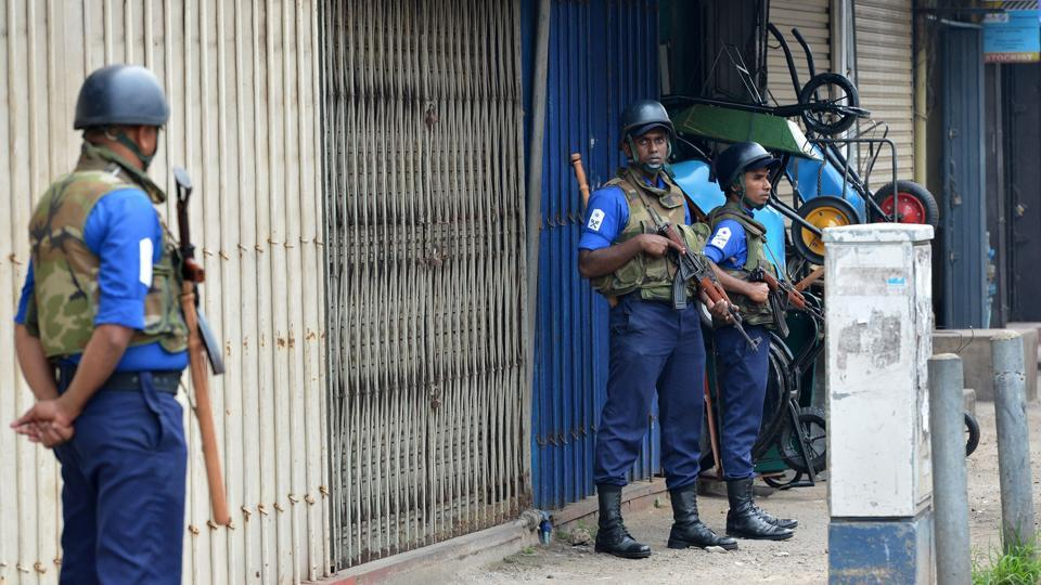 Sri Lankan Navy soldiers stand guard next to shops that have been closed in protest following deadly communal violence in other parts of the country, in Sri Lanka's capital Colombo on March 9.