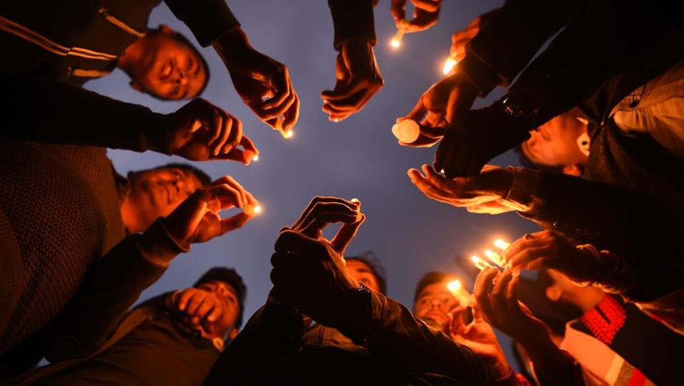 Nepali people take part in a candle light vigil in honour of the plane crash victims in Kathmandu on March 13, 2018, a day after the deadly crash of a US-Bangla Airlines plane at the international airport.
