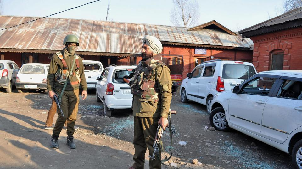 Police personnel stand near vehicles damaged in a blast caused by a grenade allegedly hurled by militants in Pulwama.