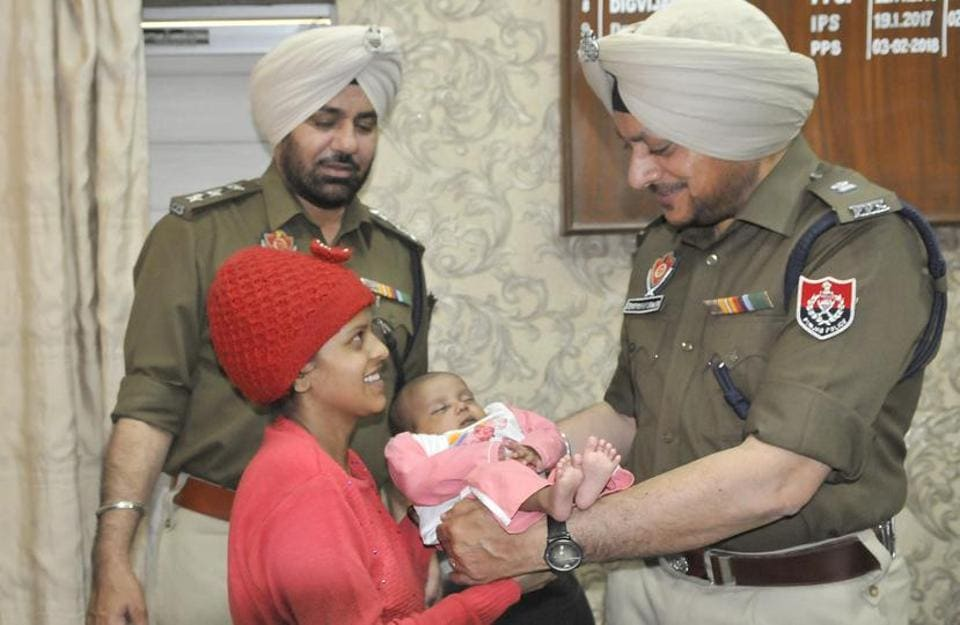 Police officials handing over the rescued child to his mother in Ludhiana on Wednesday.
